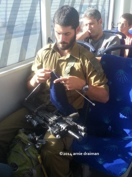 Soldier-knitting-with-assult-rifle-on-the-bus-Arnie-Draiman-550x733